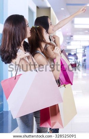 Photo of three beautiful teenage girls pointing at a store while carrying shopping bags
