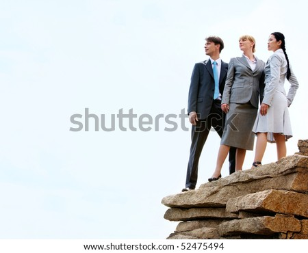 Photo of three business partners standing on the mountain top with cloudy sky above them - stock photo