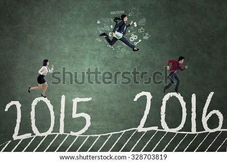 Photo of three businesspeople running and compete to reach numbers 2016 - stock photo