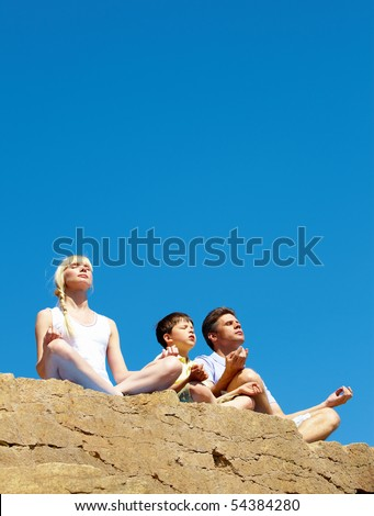 Photo of three family members sitting on cliff in pose of lotus on summer day
