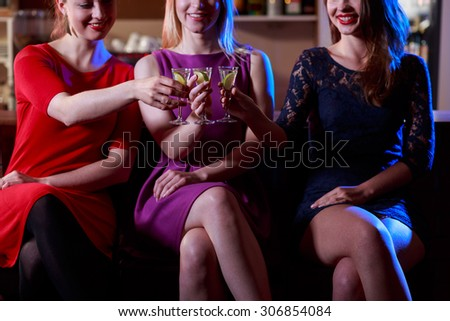 Photo of three friends sitting at bar with drinks