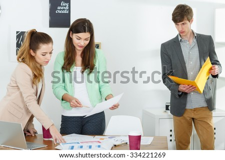 Photo of three inventive workers preparing business presentation