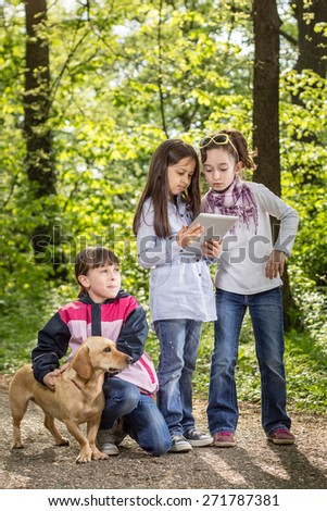 Photo of three little girls outdoor with a dog - stock photo