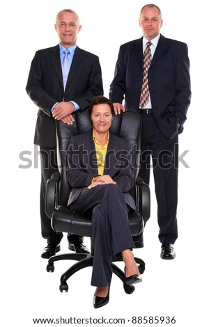 Photo of three mature business people, two businessmen standing behind the businesswoman who is sat on a leather chair, isolated on a white background. - stock photo