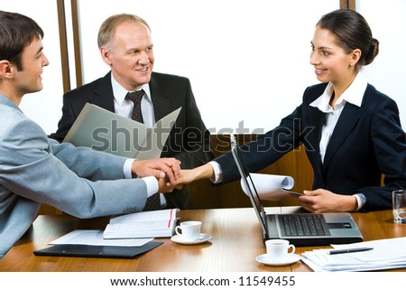 Photo of three partners holding the hands in the office - stock photo