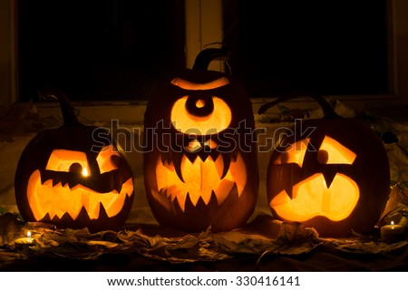 Photo of three pumpkins for Halloween. Embittered, a Cyclops and the scared pumpkin against autumn leaves and candles - stock photo