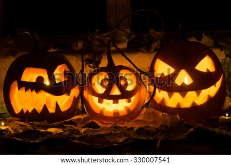 Photo of three pumpkins for Halloween. Embittered, cheerful with a smile and evil pumpkin against autumn leaves and candles - stock photo