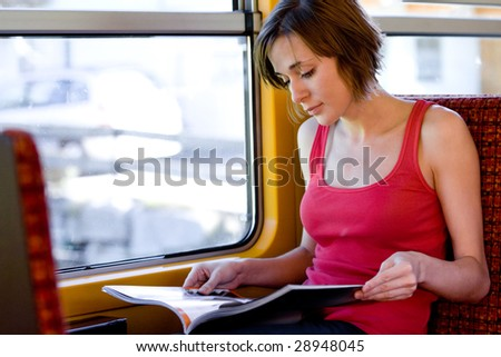 Photo of traveling passenger reading magazine in train by the window