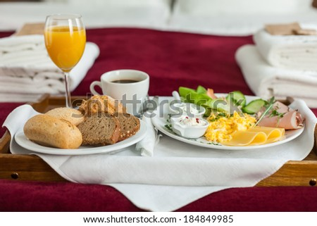Photo of tray with english breakfast food on the bed inside a bedroom - stock photo