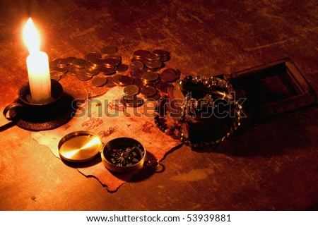 Photo of treasure map with compass, candle, box and golden coins - stock photo