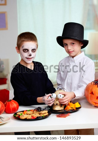 Photo of twin boys holding spooky eyes just in skull eye-sockets and looking at camera - stock photo