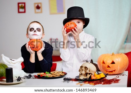 Photo of twin eerie boys holding Halloween pumpkins by their faces and looking at camera - stock photo