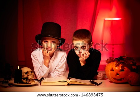 Photo of twin eerie boys looking at camera in dark Halloween night - stock photo