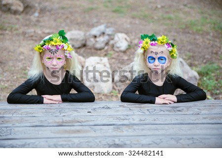 Photo of twin girls with black clothing and sugar skull makeup sitting in front of a table outdoors - stock photo
