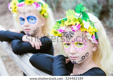 Photo of twin girls with sugar skull makeup leaning on a wooden fence - stock photo