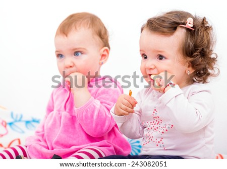 Photo of two adorable baby sitting on the bed and nibbles - stock photo