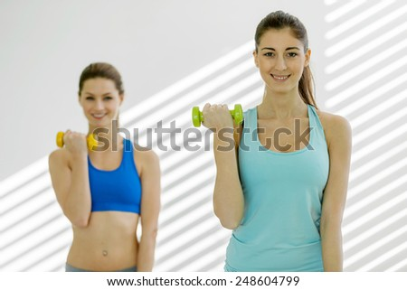 Photo of two attractive young women doing exercises with dumbbells in gym - stock photo