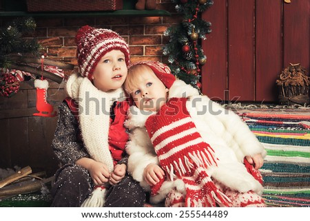 Photo of two beautiful children playing in a Christmas garden - stock photo