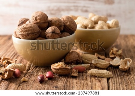 Photo of two bowls, one with walnuts and second with peanuts placed on old worn wooden table with white background and with shells and nuts around. - stock photo