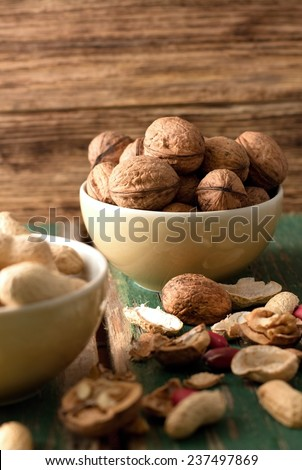 Photo of two bowls, one with walnuts in focus and second with peanuts and with shells and nuts around. Everything is placed on green worn wooden board and with another board in background. - stock photo
