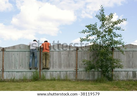 Photo of two boys on the fence looking for something - stock photo