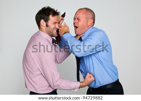Photo of two businessmen fighting against a plain background, part of a series see my portfolio for them shaking hands and hugging. - stock photo