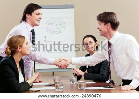 Photo of two businessmen handshaking while female employees applauding to them