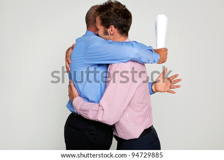 Photo of two businessmen hugging each one holding a contract, part of a series see my portfolio for them fighting. - stock photo