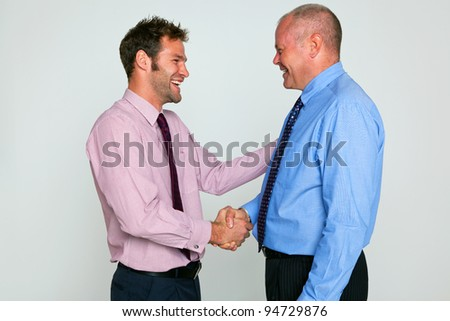 Photo of two businessmen shaking hands against a plain background, part of a series see my portfolio for images of them fighting. - stock photo
