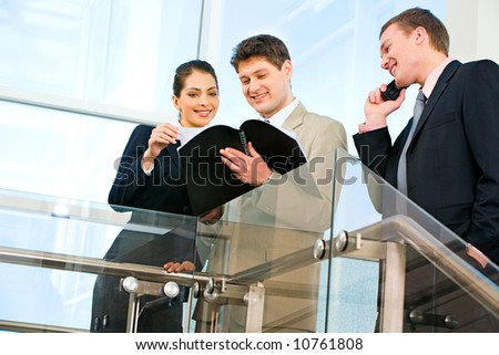 Photo of two businesspeople looking at business plan with smiles in the office with their business partner speaking on the phone near by - stock photo