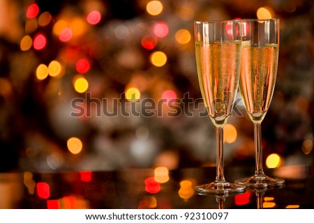 photo of two champagner glasses on glass table with bokeh background - stock photo