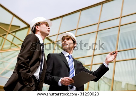 Photo of two co-workers discussing new project with modern building at background - stock photo