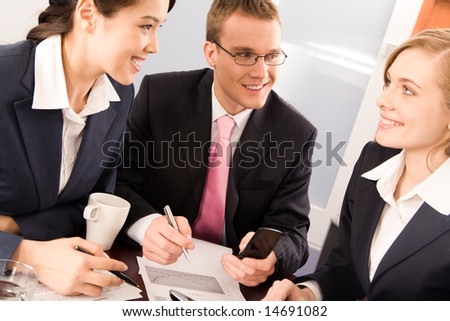 Photo of two confident business people looking at smiling woman in office