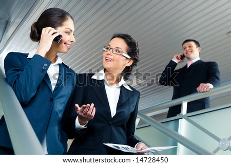 Photo of two confident businesswomen walking down stairs and speaking in office building with calling man at background - stock photo