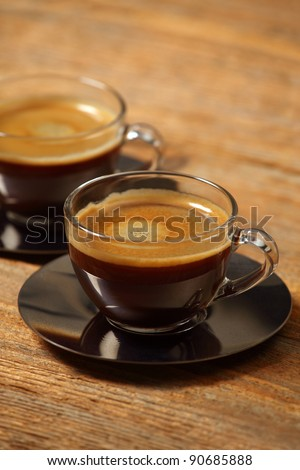 Photo of two cups of espresso on an old wooden table.  Selective focus on first cup. - stock photo