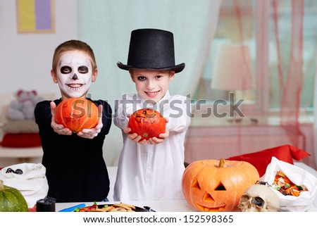 Photo of two eerie boys with Halloween pumpkins - stock photo