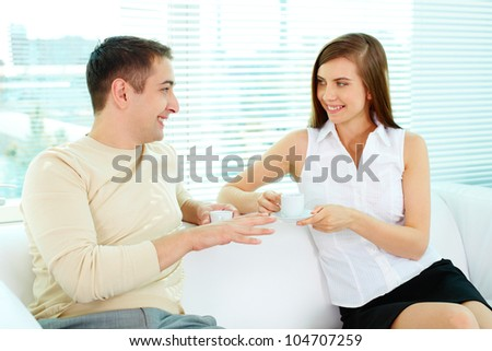 Photo of two friendly business partners in casual clothes talking while sitting in office - stock photo