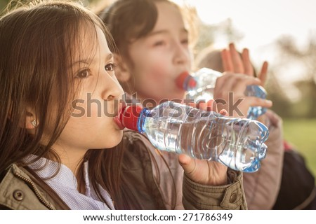 Photo of two girls drinking water from the PET bottle - stock photo