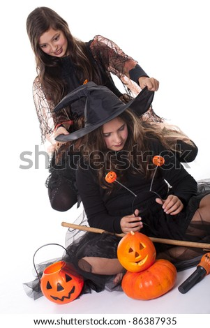 Photo of two girls in halloween costume, broom and pumpkin and having fun - stock photo