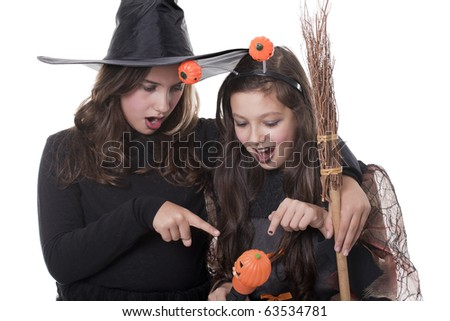 Photo of two girls in halloween costume,  broom and pumpkin looking surprised - stock photo