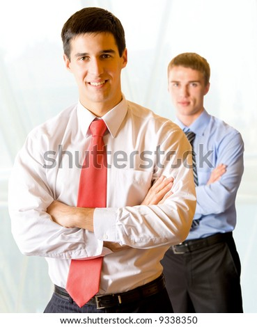 Photo of two happy businessmen in office