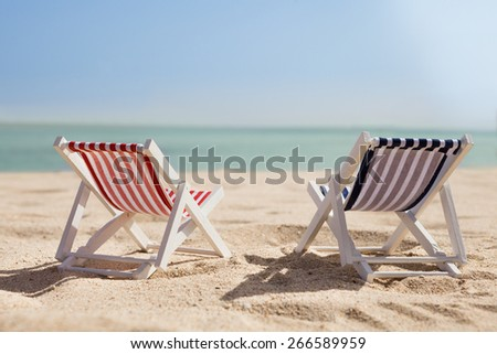 Photo Of Two Miniature Deckchairs On Sunny Beach