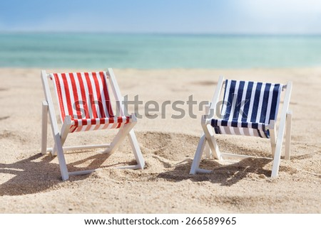 Photo Of Two Miniature Deckchairs On Sunny Beach - stock photo