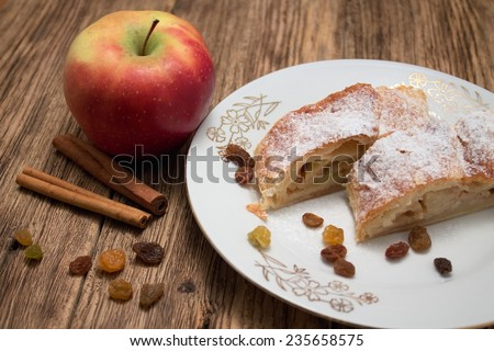 Photo of two portions of apple pie strudel on white plate with golden motif on old wooden board with cinnamon and raisins around and with one red apple near the plate. - stock photo