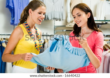 Photo of two pretty women choosing clothes in the store - stock photo