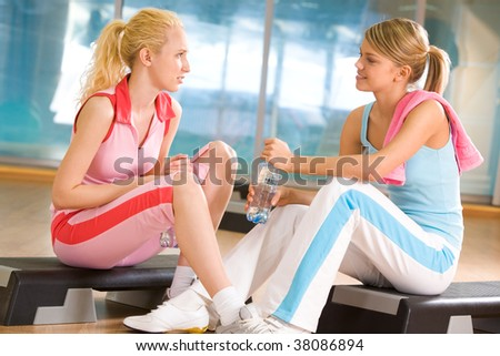 Photo of two teenage girls sitting in the sports gym and communicating - stock photo