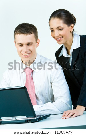 Photo of two young business people looking at the laptop