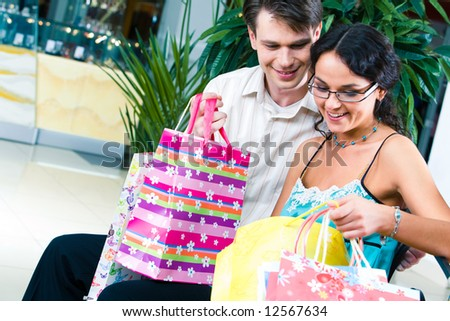 Photo of two young people looking into the shopping bag in the trade centre - stock photo