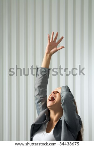 Photo of unhappy female shouting with her arm raised in pray - stock photo