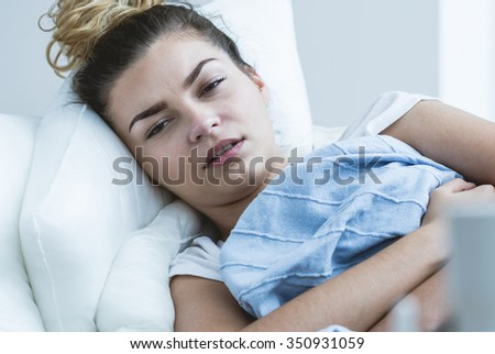 Photo of unwell girl with flu laying in bed